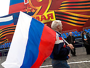 Mann mit der russischen Flagge vor der für die Militärparade aufgebauten Tribüne auf dem Roten Platz am Tag der großen Siegerparade.<br /> <br /> Man with the Russian flag infront of the big tribune prepared for the Military Parade at Red Square during the day of the Victory Parade in Moscow.