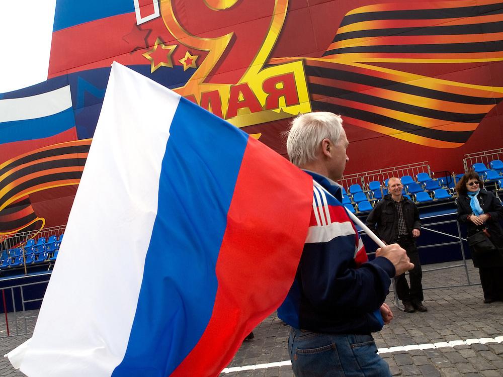 Mann mit der russischen Flagge vor der für die Militärparade aufgebauten Tribüne auf dem Roten Platz am Tag der großen Siegerparade.<br /> <br /> Man with the Russian flag infront of the big tribune prepared for the Military Parade at Red Square during the day of the Victory Parade in Moscow.