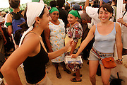 10 SEPTEMBER 2003 - CANCUN, QUINTANA ROO, MEXICO: Anti-globalization protestors opposed to the World Trade Organization and globalization dance while Mexican women watch them at an anti-WTO rally in the city of Cancun, Quintana Roo, Mexico. Tens of thousands of people opposed to the WTO have come to this Mexican resort city to protest the 5th Ministerial meeting of the World Trade Organization. The WTO meetings are taking place in the hotel zone of Cancun, about 10 miles from the protestors.  PHOTO BY JACK KURTZ