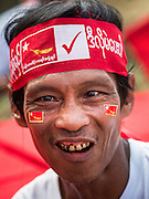 25 OCTOBER 2015 - SHWEPYITHAR, MYANMAR: A NLD supporter in Shwepyithar, Myanmar, waits for a NLD motorcade to come to the small town about 90 minutes from Yangon. Political parties are in fill campaign mode in Myanmar (Burma). National elections are scheduled for Sunday Nov. 8. The two principal parties are the National League for Democracy (NLD), the party of democracy icon and Nobel Peace Prize winner Aung San Suu Kyi, and the ruling Union Solidarity and Development Party (USDP), led by incumbent President Thein Sein. There are more than 30 parties campaigning for national and local offices.     PHOTO BY JACK KURTZ