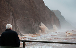© Licensed to London News Pictures. 27/01/2016. Sidmouth, UK.  A man looks on as waves batter the sea cliffs at Sidmouth as the tail end of storm Jonas hits the UK. Photo credit: Peter Macdiarmid/LNP