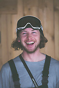 Head and shoulder portrait of a male snowboarder outside a traditional woodedn chalet, Refuge De Bostan, in Vallée de la Manche in Morzine / Portes du Soleil ski area on 22nd March 2017 in France