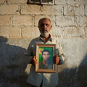 August 12, 2012 - Kafa Safra, Efrin, Syria: Barakat Gadalum, father of a dead Kurdistan Workers' Party (PKK) fighter, poses with his son's portrait. Around five thousand Syrian Kurdish attended the funeral and ceremony of martyrdom of Taliz Gadalum, killed days earlier during combat against the Turkish army...PKK has been fighting an armed struggle against the Turkish state for an autonomous Kurdistan and greater cultural and political rights for the Kurds in Turkey, Iraq, Syria and Iran. Founded on 27 November 1978 in the village of Fis, was led by Abdullah Öcalan. The PKK's ideology was originally a fusion of revolutionary socialism and Kurdish nationalism - although since his imprisonment, Öcalan has abandoned orthodox Marxism. The PKK is listed as a terrorist organization by Turkey, the United States, the European Union and NATO. (Paulo Nunes dos Santos)
