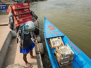 21 APRIL 2014 - CHIANG SAEN, CHIANG RAI, THAILAND: Burmese stevedores load fertilizer and building supplies onto a small river freighter in Chiang Saen, Chiang Rai province, Thailand. Chiang Rai province in northern Thailand is facing a drought this year. The 2014 drought has been brought on by lower than normal dry season rains. At the same time, closing dams in Yunnan province of China has caused the level of the Mekong River to drop suddenly exposing rocks and sandbars in the normally navigable Mekong River. Changes in the Mekong's levels means commercial shipping can't progress past Chiang Saen. Dozens of ships are tied up in the port area along the city's waterfront.      PHOTO BY JACK KURTZ