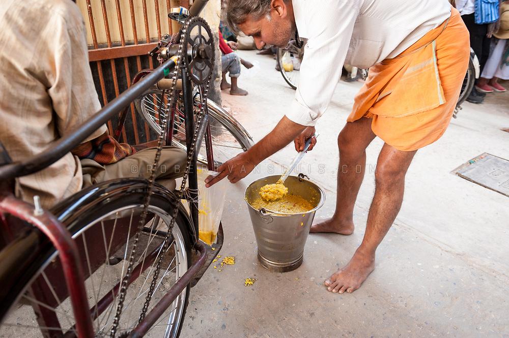 Handing out lentils to the disabled at Mumukshu Bhawan hospice, Varanasi, India. Photo © robertvansluis.com
