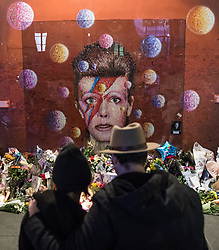 © Licensed to London News Pictures. 10/01/2017. London, UK. A couple stand arm-in-arm in front of the mural of David Bowie in Brixton, south London, on the first anniversary of the star's death. Photo credit: Rob Pinney/LNP