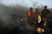 Boys stand in a cloud of smoke by burning pieces of plastic near the Agbogboloshie market in Accra, Ghana on Thursday August 21, 2008..Using pieces of plastic from computer casings and foam from old refrigerators, boys build fires to burn plastic off cables that come from computers and other electronics. They recover the copper and sell it for about $4 a kilo.
