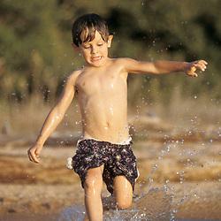 Texas:  Four year (4) old boy running through water at Lake Buchanan in central Texas. MR July 2001 ©Bob Daemmrich