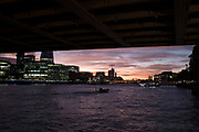 Sunset view underneath Tower Bridge from the River Thames in London, England, United Kingdom. Taken from a riverboat offering a unique view.