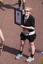 © Licensed to London News Pictures. 21/04/2013. London, England. Picture: Runner in a school uniform is attempting Guinness World Record. Celebrity Runners and Fun Runners finish the Virgin London Marathon 2013 race in the Mall, London. Many wore black ribbons to pay their respect for those who died or were injured in the Boston Marathon. Photo credit: Bettina Strenske/LNP