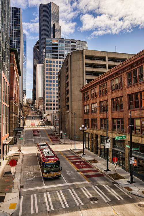 A public transit bus makes its way along a starkly deserted Columbia Street. (April 4, 2020).