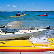Sea kayaks in Casco Bay off the beach along the Eastern Promenade. Portland, Maine