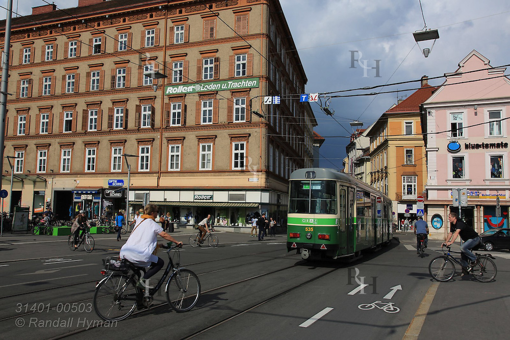 Tram (standard gauge, 600-volt DC powered) passes cyclists in the central shopping district on a June day in downtown Graz, Austria.