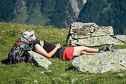 A hiker relaxes in the alpine meadows (alps) of Lötschental above Lauchernalp gondola lift station in canton Valais/Wallis, Switzerland, Europe. Kandersteg is a great base for hiking: an epic hike from Selden in Bern canton traverses Lötsch glacier and Lötschenpass (Lötschepass) to neighboring Lötschental in Valais canton; hiking poles are recommended for snow and rocks. The walk starts with a reserved Postbus ride from Kandersteg to Selden (in Gasterntal / Gasteretal / Gasterental), climbs 1350 meters, descends 925 m, and ends 13 km later at Lauchernalp lift station, which descends to Wiler in Lötschental, to reach Goppenstein via Postbus, back to Kandersteg via train. You can also reverse the route or stay overnight in dorms at Lötschepass hut.