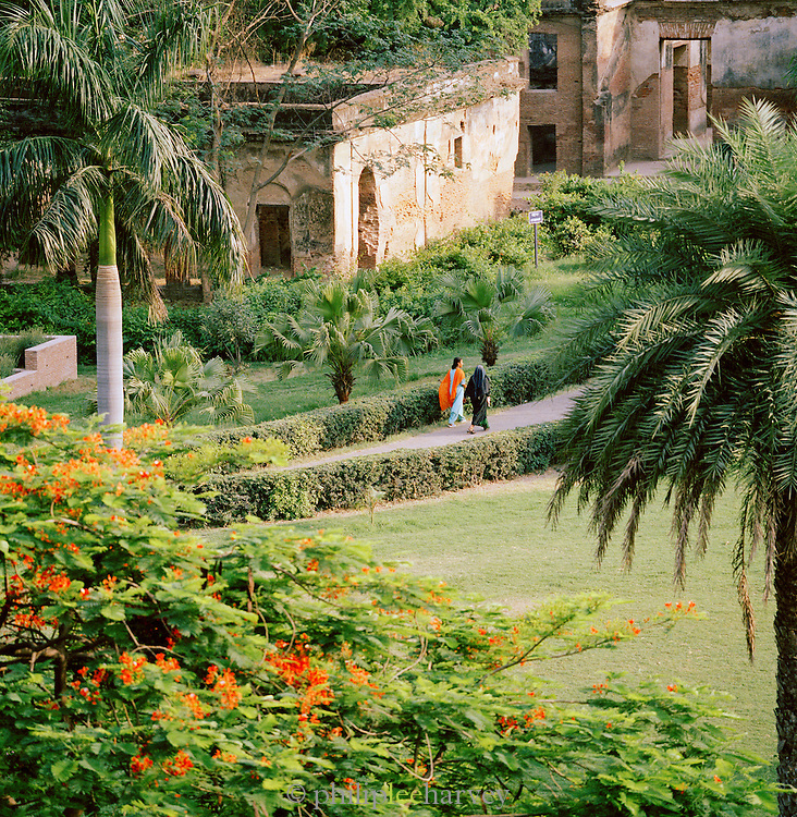 Indian women walking in gardens of the Residency Hotel, originally constructed in order to serve as the residence for the British Resident General who was a representative in the court of Nawab. Lucknow, Uttar Pradesh, India