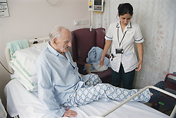 Female occupational therapist assessing elderly patient's mobility and independence by observing bed transfer,