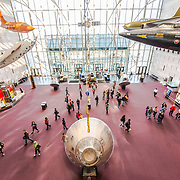 Elavated view of the main foyer inside the entrance at the Smithsonian Institution's National Air and Space Museum on the National Mall in Washington DC. The lunar module at the bottom of the frame is the original Apollo XI re-entry vehicle, while the orange plane at top left was Chuck Yeager's Bell X-1 aircraft in which he broke the sound barrier for the first time in level flight. The Air and Space Museum, which focuses on the hsitory of aviation and space exploration, is one of the most visited museums in the world.