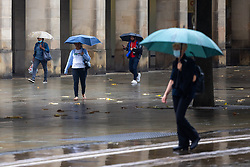 © Licensed to London News Pictures. 27/07/2021. Manchester, UK. People are seen carrying umbrellas in and around St Peters Square in Manchester City Centre . Photo credit: Joel Goodman/LNP