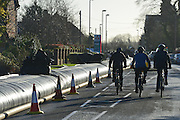 © Licensed to London News Pictures. 16/02/2014. Chertsey, UK An Aqua dam has been erected along Bridge Road in Chertsey, Surrey. At almost half a mile long and four feet high the dam is designed to protect 200 houses on the South Side of the street. The Environment Agency has said there is nothing they can do to protect the houses on the North side if flood water from the River Thames rises. . Photo credit : Stephen Simpson/LNP