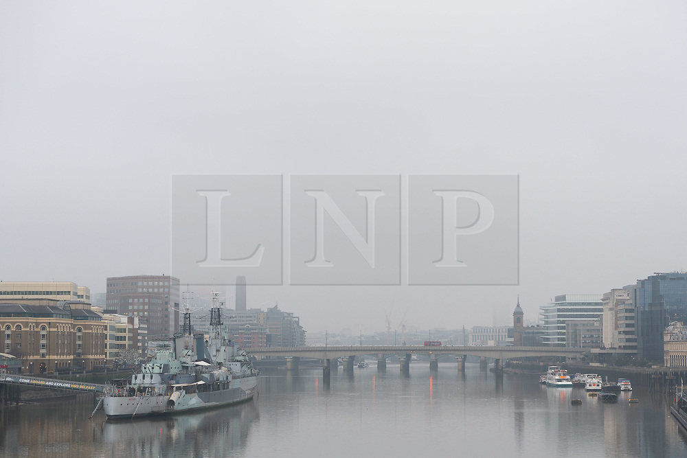 © Licensed to London News Pictures. 17/12/2017. London, UK. A bus travels across London Bridge during freezing fog this morning. The capital experienced another very cold night with freezing weather. Photo credit: Vickie Flores/LNP