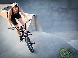 United States, Washington, Seattle, Jefferson Park, young woman riding bicycle in skateboard park