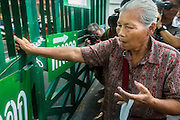 """01 FEBRUARY 2014 - BANGKOK, THAILAND: A Thai voter tries to get through a locked gate at the Din Daeng polling place in Bangkok. Thais went to the polls in a """"snap election"""" Sunday called in December after Prime Minister Yingluck Shinawatra dissolved the parliament in the face of large anti-government protests in Bangkok. The anti-government opposition, led by the People's Democratic Reform Committee (PDRC), called for a boycott of the election and threatened to disrupt voting. Many polling places in Bangkok were closed by protestors who blocked access to the polls or distribution of ballots. The result of the election are likely to be contested in the Thai Constitutional Court and may be invalidated because there won't be quorum in the Thai parliament.    PHOTO BY JACK KURTZ"""