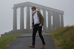 © Licensed to London News Pictures.  09/09/2021. Edinburgh, Scotland. A man walks in the ran at Calton Hill in Edinburgh. Scotland is currently the Covid capital of the UK with 17 out of 20 hotspots north of the border. Photo credit: Marcin Nowak/LNP