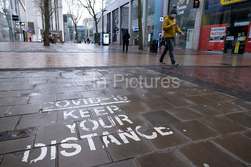 National coronavirus lockdown three begins on New Street in Birmingham city centre, which is deserted apart from a few people in an area which is normally busy with shoppers on 6th January 2021 in Birmingham, United Kingdom. Following the recent surge in cases including the new variant of Covid-19, this nationwide lockdown, which is an effective Tier Five, came into operation today, with all citizens to follow the message to stay at home, protect the NHS and save lives.