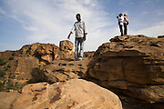 Guide Foussani Guindo helps tourists to climb rocks near begnimato village. The Dogon Country is the most visited part of Mali with tourists visiting its tipical  villages that can be located on the cliff, on the sandy plain or in the rocky plateau