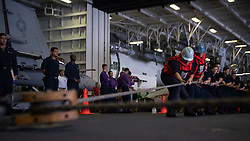 180815-N-IL409-0247 PACIFIC OCEAN (Aug. 14, 2018) Sailors heave a line during a replenishment-at-sea in the hangar bay aboard the Nimitz-class aircraft carrier USS John C. Stennis (CVN 74). John C. Stennis is underway conducting routine operations in the U.S. 3rd Fleet area of operations. (U.S. Navy photo by Mass Communication Specialist Seaman Apprentice Joshua Leonard/Released)