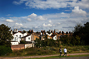 Two girls walk a dog in a park overlooking East London housing. This is a poor area of Tower Hamlets. The borough has a population of 220,000, which includes one of the highest ethnic minority populations in the capital.