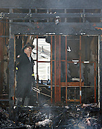 A New Windsor fire inspector looks over the inside of a home destroyed by fire on Independence Drive in Vails Gate on Friday, Aug. 16, 2013.
