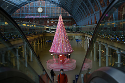 © Licensed to London News Pictures. 07/11/2020. London, UK. St. Pancras International, in partnership with Elan Cafe, have unveiled this year's St. Pancras Christmas tree, titled 'The Tree of Hope'. It's located within the concourse at the international station in central London. The 34ft carousel-themed tree is decorated with ribbons, featuring messages of love and hope from NHS staff and key workers who have worked throughout the COVID-19 pandemic. Photo credit: Dinendra Haria/LNP