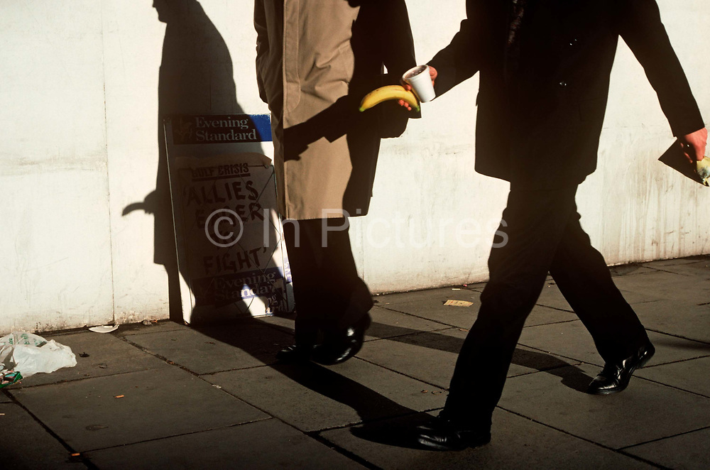 A businessman strides along a London street holding a banana whose shadow appears to be part of another man's anatomy. As strong sunlight shines on this part of a London pavement, we see the confident stride of the man in the foreground, probably on his way back from a lunchtime stroll and returning to his office with the fresh fruit and a sandwich. What cannot be anticipated by the viewer, or by the second man, is that the banana has superimposed itself to the exact place of his groin area. The banana, by its very curved shape has long been the butt of sexual innuendo and double-entendre. The surrogate penis being the perfect adult pun.