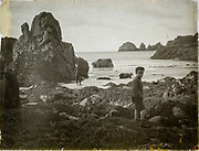 Magic lantern slide two boys playing on rocky beach circa 1900 location not known, presumed to be England, UK perhaps Cornwall