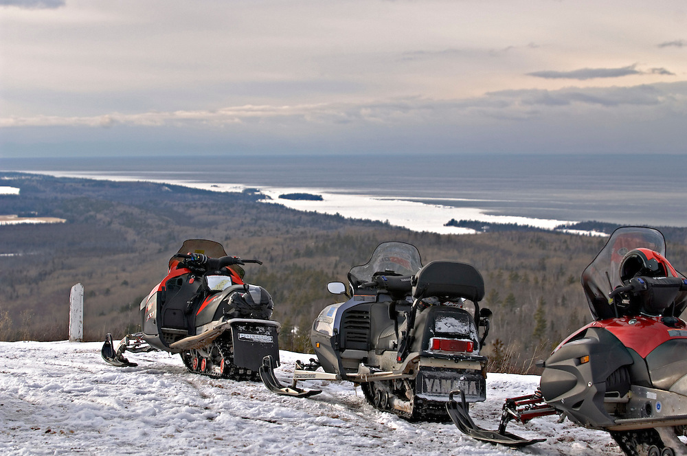 Snowmobilers parked atop Brockway Mountain overlooking a valley and Lake Superior near Copper Harbor Michigan.