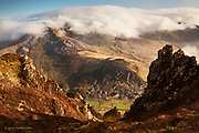 Banks of cloud roll in from the Irish Sea and curl over the top of the Nantlle Ridge in Snowdonia, North Wales, before evaporating again over the Nantlle valley at Drws y Coed. Taken from the a precipitous crag of Craig y Bera on the adjacent mountain of Mynydd Mawr.
