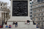 Tourists sit beneath The Battle of Cape St Vincent by Musgrave Watson and William F. Woodington, the relief on the west face of the plinth on Nelson's Column in Trafalgar Square.