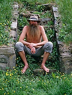 Mature man with long beard sitting on steps with hand on knee, portrait