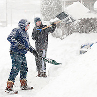 Kevin and Jedrek Laurent of Winter Street shovel through piles of snow left by the plows during the height of the Nor'Easter that stormed through the Lakes Region Wednesday.  (Karen Bobotas/for the Laconia Daily Sun)