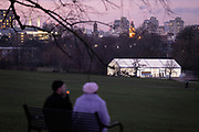 South Londoners sit on a park bench overlooking the backdrop of construction at Nine Elms and the temporary facility serving as an asymptomatic COVID-19 testing centre is located in Brockwell Park in Lambeth, during the third pandemic lockdown, on 21st January 2021, in London, England. Government ministers are to discuss proposals to pay anyone in England who tests positive for Covid-19 £500 to self-isolate. Many workers are currently strugling financially because low paid workers cannot afford to self-isolate.