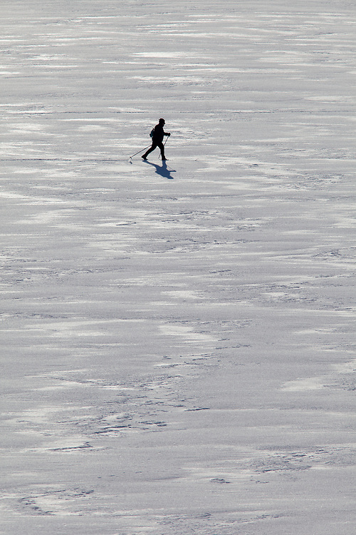 Lone cross country skier on the frozen lake surface of Palisades Dam cruises wherever he likes.  Licensing and Open Edition Prints