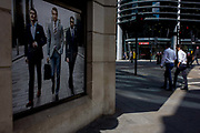Men in shirtsleeves walk past a stylish clothing shop for businessmen on a poster in the City of London. The two businessmen stride past very good-looking and stylish men wearing sharp suits - the latest in 2015 city fashion. The street is in the City of London, the capital's financial heart.