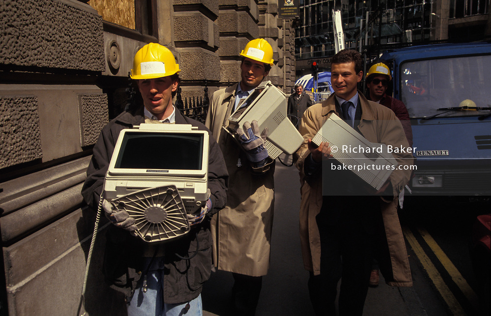 City workers carry office possessions including computer hard drives and files that were damaged by the IRA bomb that devastated the City of London's Bishopsgate area in 1993, on 26th April 1993, in London, England. Allowed to return to their desks to recover their data and working paperwork, they walk through the ancient streets en route to new emergency office elsewhere in the capital. The Irish Republican Army (IRA) exploded a truck bomb on Bishopsgate. Buildings up to 500 metres away were damaged with one and a half million square feet (140,000 m) of office space being affected and over 500 tonnes of glass broken. Repair costs reached approx £350 million. It was said that Roman remains could be viewed at the bottom of the pit the bomb created. One person was killed when the one ton fertiliser bomb detonated directly outside the medieval St Ethelburga's church.