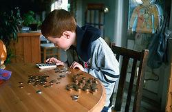 7 year old boy counting his money using a calculator at home in kitchen; UK.MR