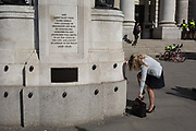 A lady stands on one leg to change her shoes beneath the WW1 memorial at Royal Exchange, on 19th April, in the City of London, England.