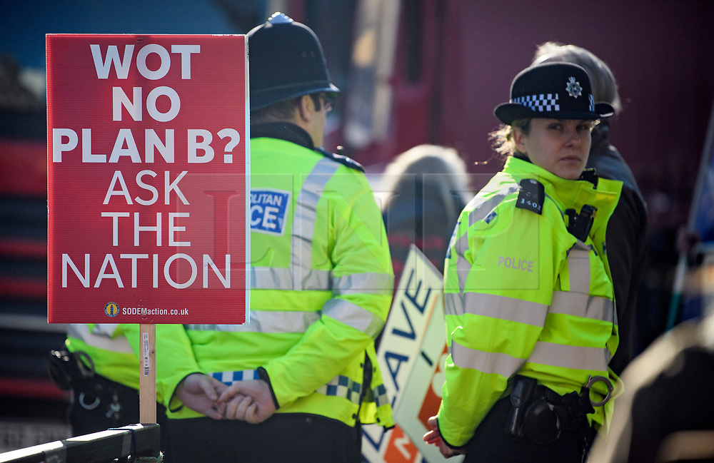 © Licensed to London News Pictures. 14/02/2019. London, UK. Police officers stand next to an anti Brexit sign outside the Houses of Parliament in Westminster, on the day that MPs are due to take part in further debates and votes on Brexit. A series of amendments are being tabled to try to change the direction of Brexit, but a vote on a deal will not be held today as was originally planned. Photo credit: Ben Cawthra/LNP
