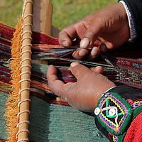 South America, Peru, Chinchero. Peruvian weaver separates strands on loom.