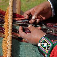 South America, Peru, Chinchero. Peruvian weaver separates strands on loom.