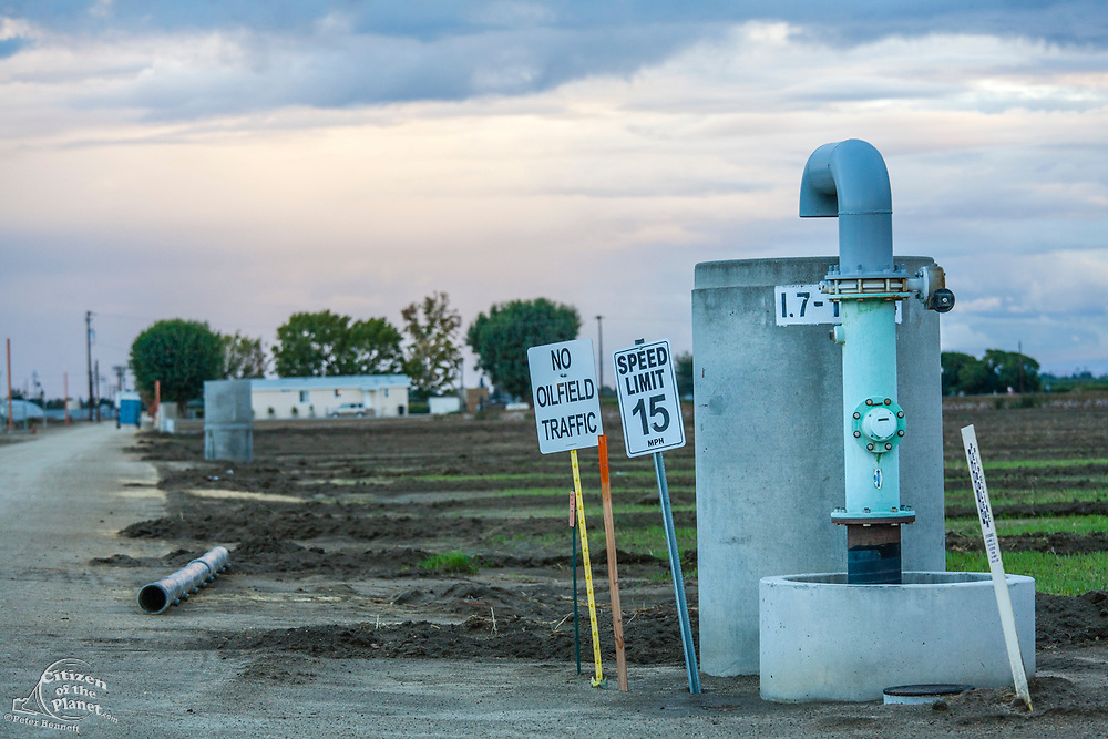 No oilfield traffic sign next to groundwater well with oil well pumpjack and cotton field in background Kern County, located over the Monterey Shale, has seen a dramatic increase in oil drilling and hydraulic fracking in recent years. San Joachin Valley, California, USA